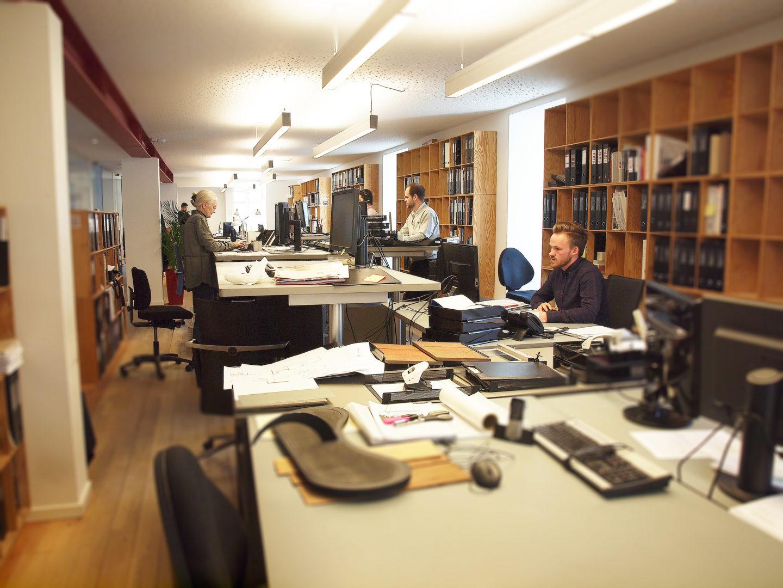 Billede af tegnestuen, hvor man kan se bygningskonstruktører, arkitekter samt vores tekniske assistent arbejdende ved deres skriveborde.